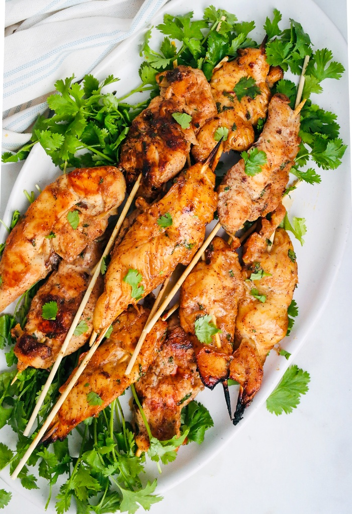 Top view of cooked chicken skewers on a white platter.