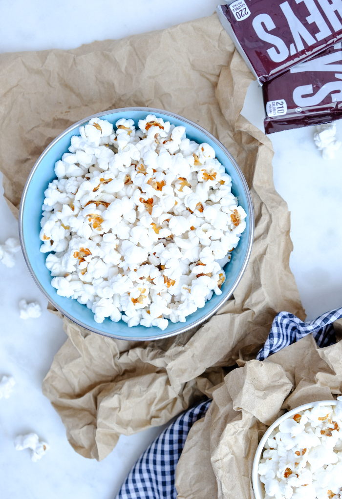 Overhead view of a bowl of popped popcorn with some chocolate bars on the side.