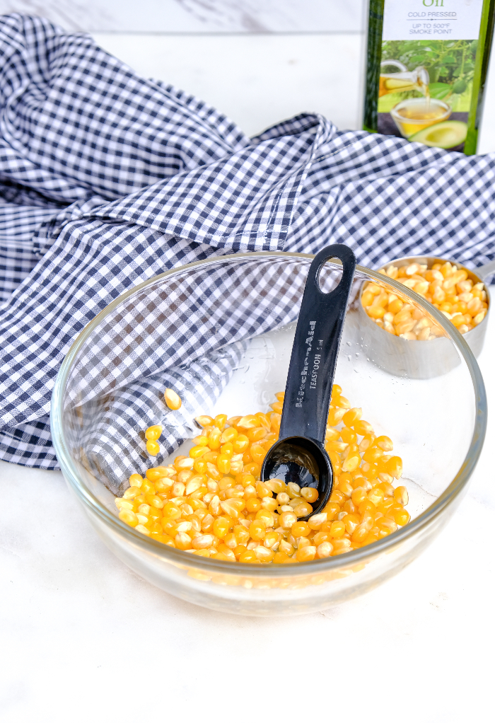 Popcorn kernels in a glass mixing bowl with oil for popping.