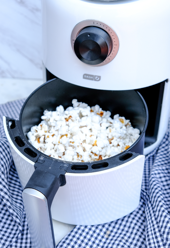 Popped popcorn in the basket of an air fryer.