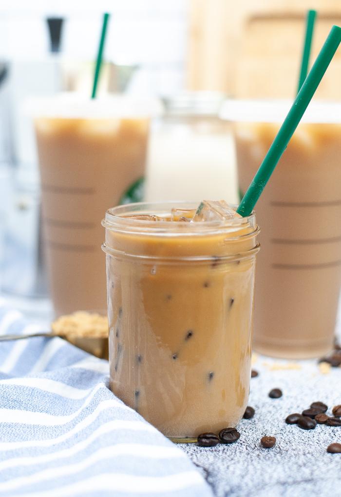 Clear Mason jar with brown sugar oat milk espresso beverage.