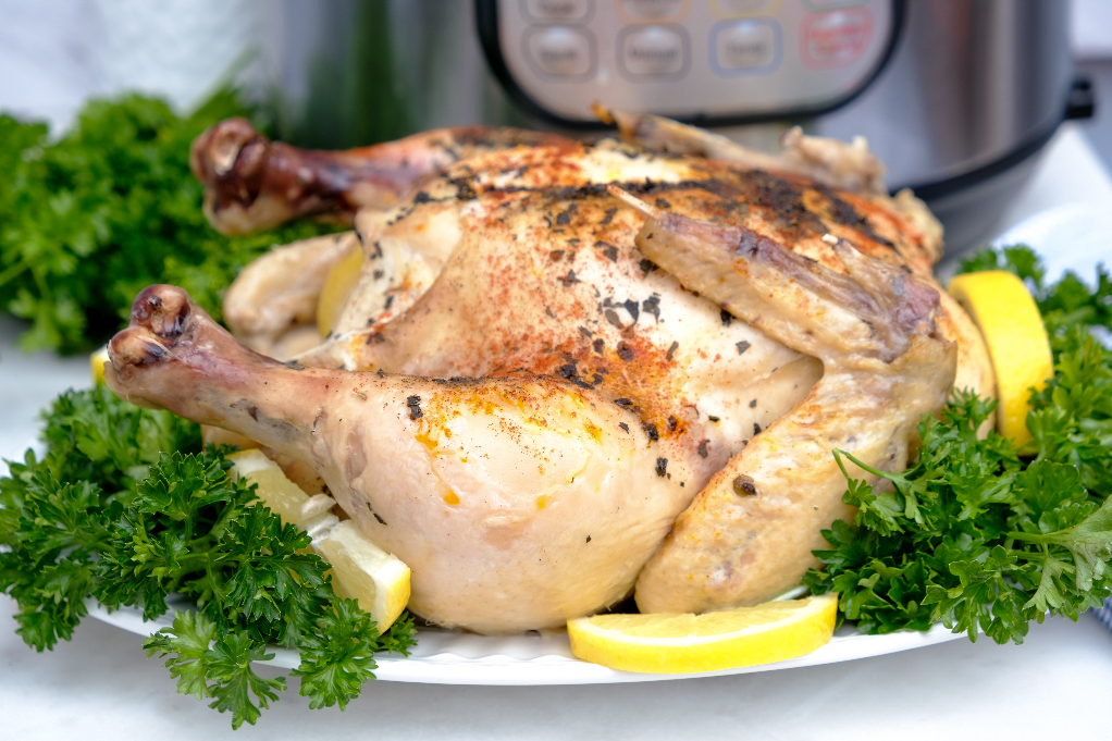 Whole chicken with lemon on a serving plate.