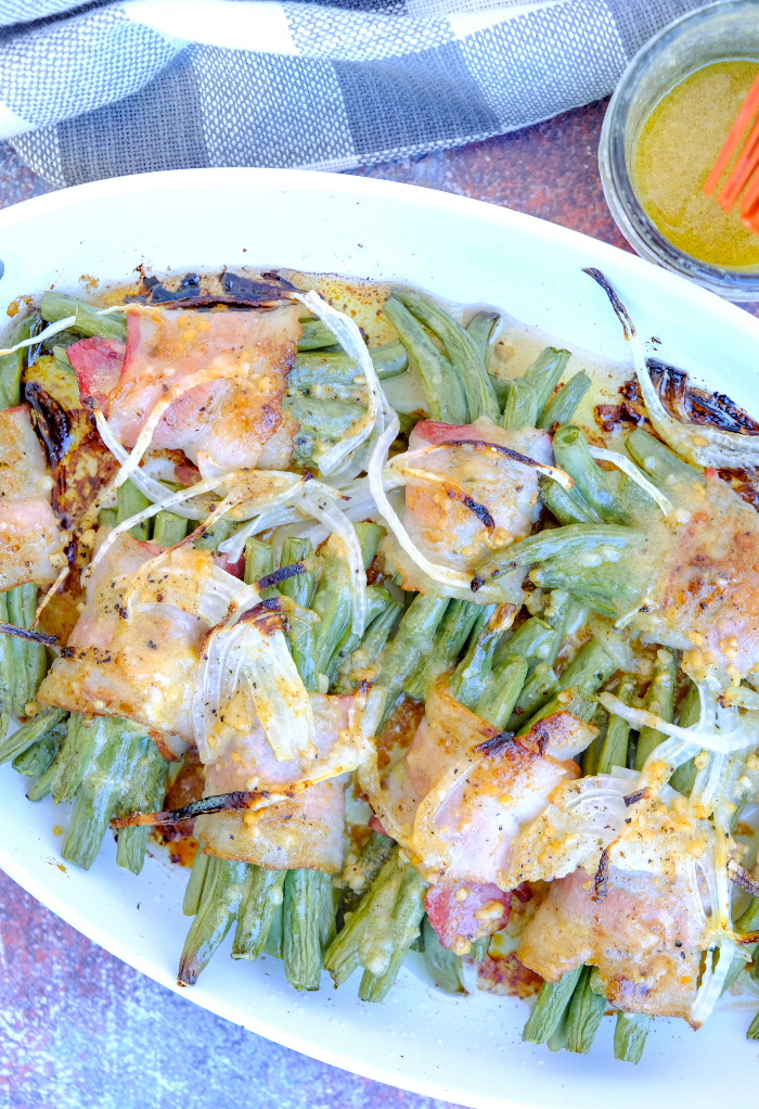 Fresh green beans wrapped in slices of bacon on a serving dish.