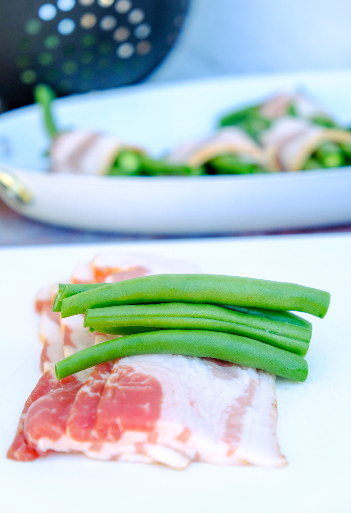 Fresh green beans placed on a slice of bacon.