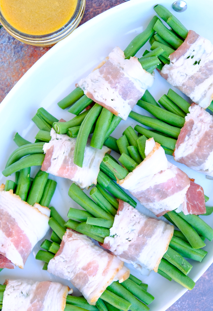 Bacon wrapped green beans on a baking pan.