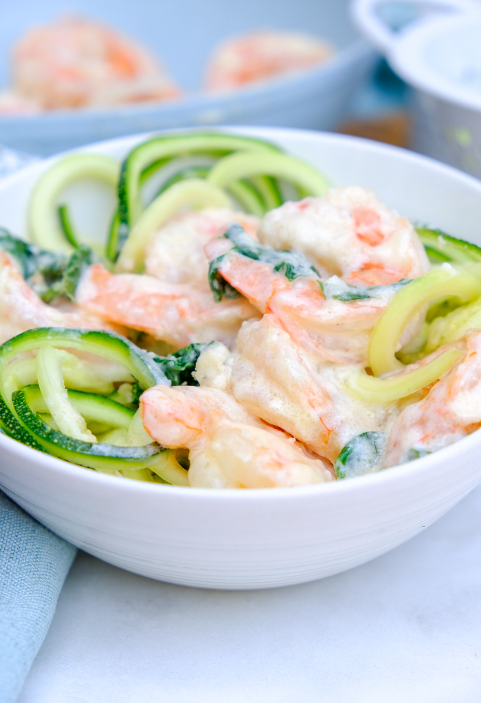 A small white bowl with shrimp and zucchini noodles.