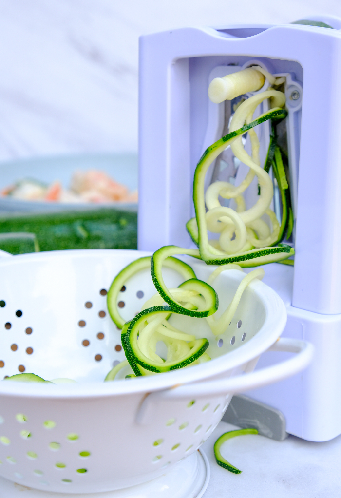 Hand held spiralizer with zucchini noodles in a white colander.