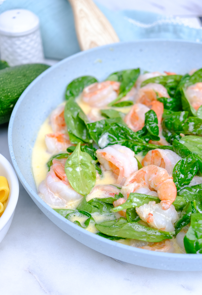 Shrimp and spinach in a skillet with Alfredo sauce.
