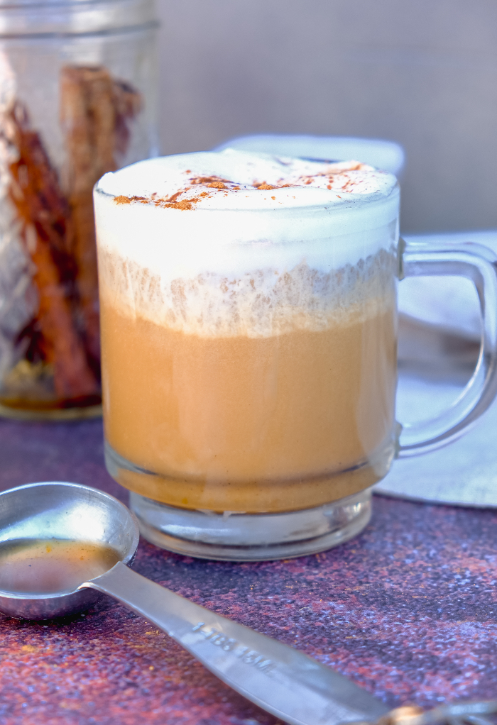 Pumpkin spice latte with whipped cream in a clear mug.