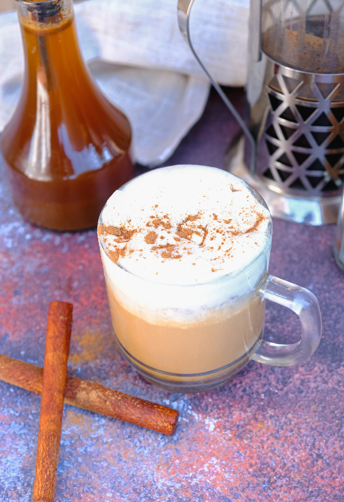 A hot mug of coffee with cinnamon sticks on the side