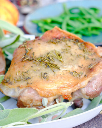 Baked turkey thighs on a white serving plate with fresh sage.